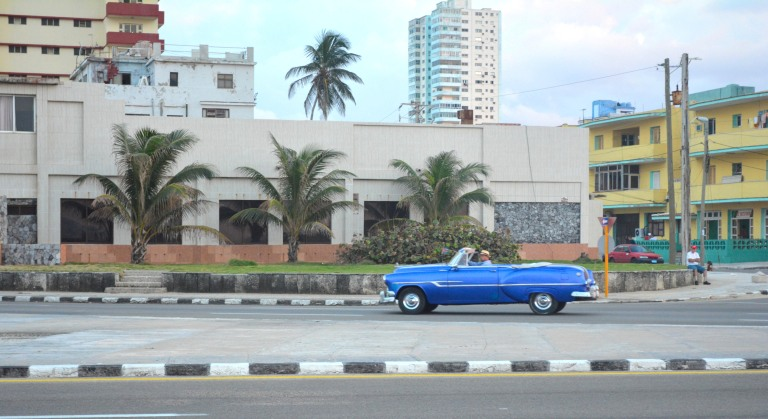 A convertible driving by the Malecon